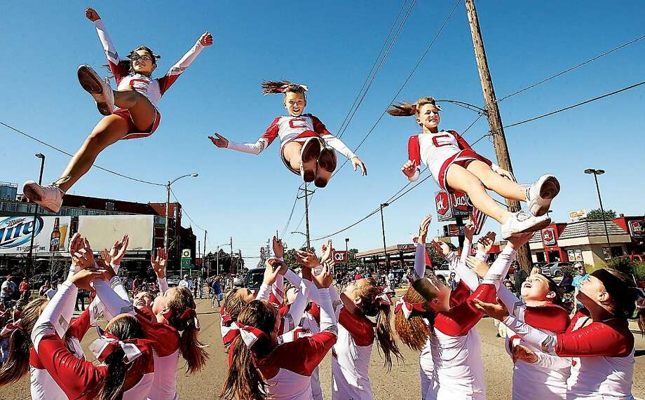 Cheerleaders from Coolidge Junior High School in Granite City, Ill.,  drop into the arms of their fellow cheerleaders after a brief demonstration during the 34th annual Granite City Labor Day Parade Monday, Sept. 2, 2013.  A large crowd was hand again this year to watch the bands, fire trucks, labor union members and politicians in the parade.  Photo: John Badman, Associated Press