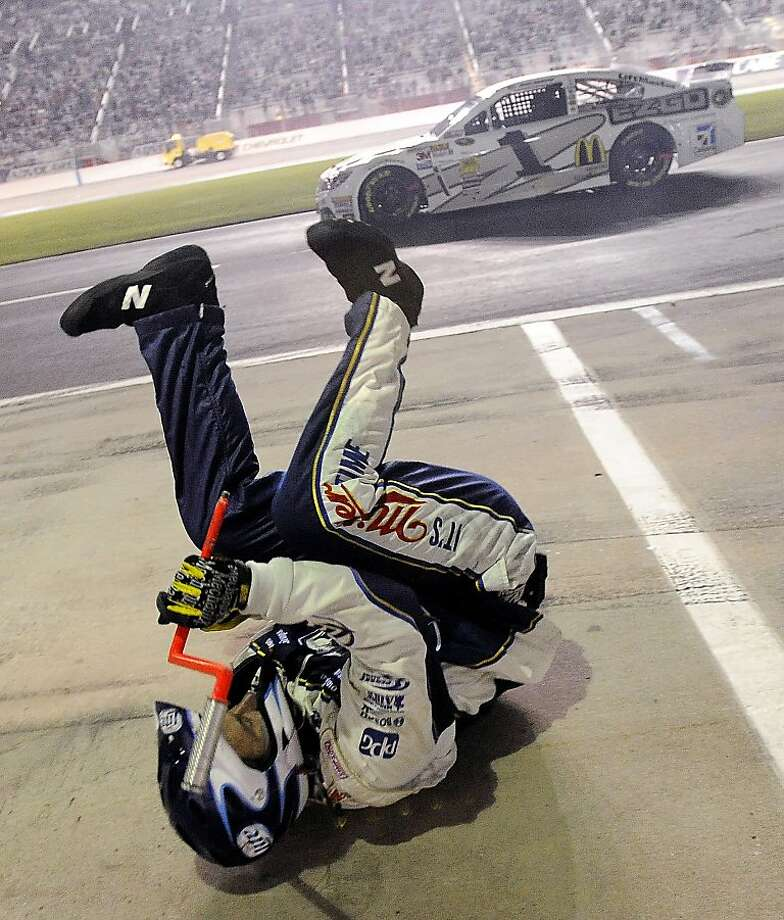 A pit crewman for Sprint Cup Series driver Brad Keselowski (2) tumbles down pit road after being knocked down during a pit stop in the NASCAR Sprint Cup Series auto race at Atlanta Motor Speedway in Hampton, Ga., Sunday, Sept. 1, 2013. At rear is Sprint Cup Series driver Jamie McMurray (1).  Photo: David Tullis, Associated Press