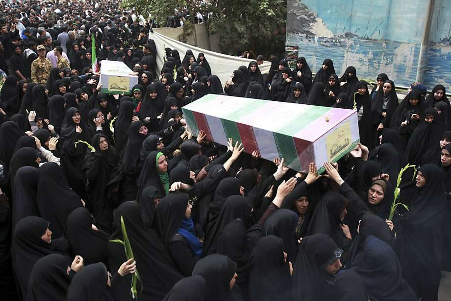Female Iranian mourners carry flag-draped coffins of two soldiers who were killed during the 1980-88 Iran-Iraq war, whose remains were recently recovered, during a funeral in Tehran, Iran, Monday, Sept. 2, 2013.  Photo: Ebrahim Noroozi, Associated Press