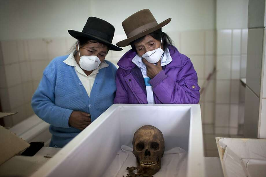 Aquilina Cardenas, right, and her sister Luciana look into the coffin containing the remains of their father in a forensic laboratory in Ayacucho, Peru. Their father is one of the Chaca residents tortured and killed on Jan. 8,1988 by Shining Path militants in retaliation for forming a self-defense committee. The remains of the victims were exhumed in 2012 from a mass grave and released to family members on June 13, 2013. A mass burial was held in Chaca two days later.  Photo: Rodrigo Abd, Associated Press