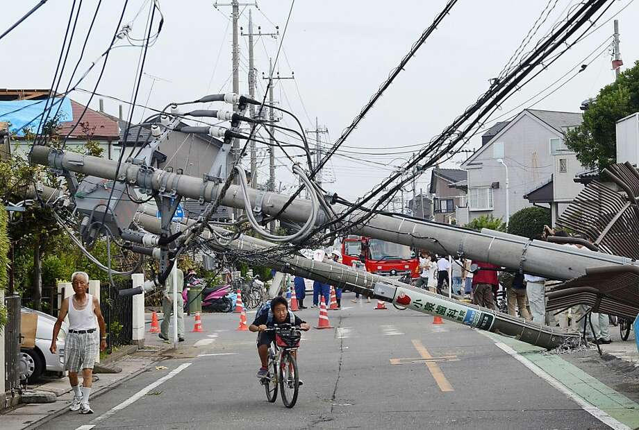 Don't forget to duck! A bicyclist rides under utility poles toppled by a tornado in Koshigaya, Japan. Dozens of people were injured and several buildings destroyed. Photo: Associated Press