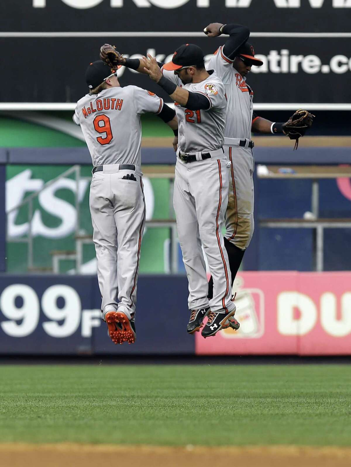 Baltimore Orioles outfielders Nate McLouth, left, Nick Markakis, center, and Adam Jones celebrate after a baseball game against the New York Yankees at Yankee Stadium, Sunday, Sept. 1, 2013, in New York. The Orioles won 7-3. (AP Photo/Seth Wenig) ORG XMIT: NYY114