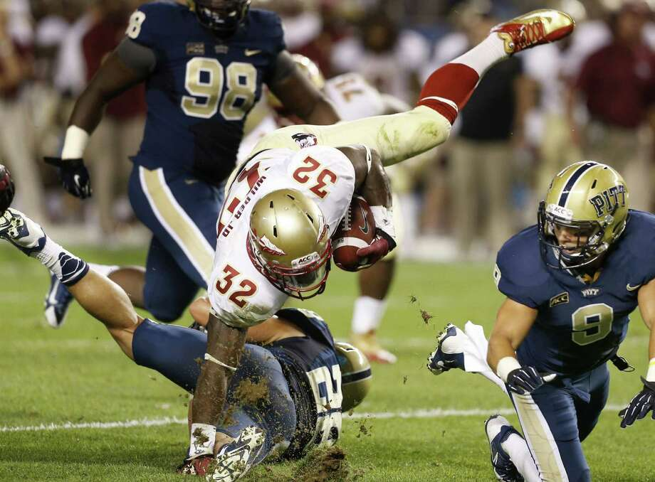 Florida State running back James Wilder tumbles over Pittsburgh linebacker Anthony Gonzalez during the second quarter. Wilder finished with 58 yards on 10 carries. Photo: Keith Srakocic / Associated Press
