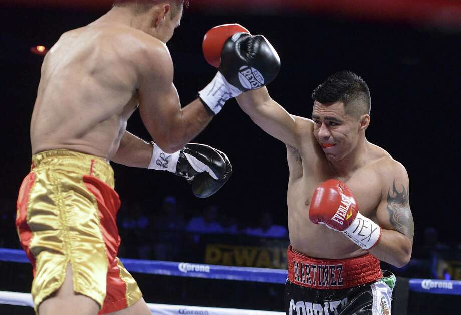 San Antonio's Raul Martinez (right) aims a right cross at Daniel Quevedo during Monday night's card at Cowboys. Photo: Billy Calzada / San Antonio Express-News