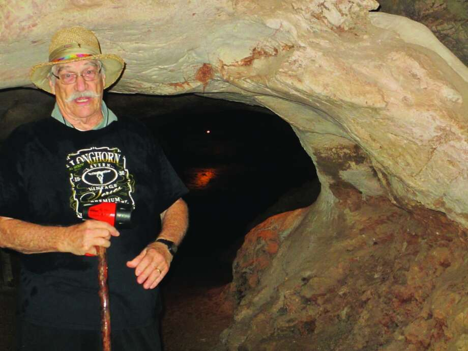 Al Gerow, wearing an American flag pin and a cross on his straw hat and carrying a walking stick and flashlight, stops to talk with a group on a tour he's leading through the Longhorn Cavern Photo: Terry Scott Bertling, San Antonio Express-News