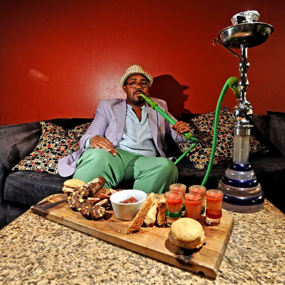 Kellen Bradford, photographed at Jerusalem Hookah Cafe. Styled by Grace Mathis. Wearing: Daniel Cremieux fedora, Ralph Lauren glasses, Rue51 blazer, Perry Ellis tunic, bracelets from People Like Shine, Daniel Cremieux pants, Stacy Adams shoes. Randy Edwards/cat5 Photo: Randy Edwards, Beaumont Enterprise