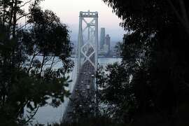 Commuters drive over the Bay Bridge western span into the city as the sunrises, Tuesday September 3, 2013, from the Yerba Buena Island, San Francisco, Calif. The bridge which ran over 8 billion dollars over budge opened early Monday night.