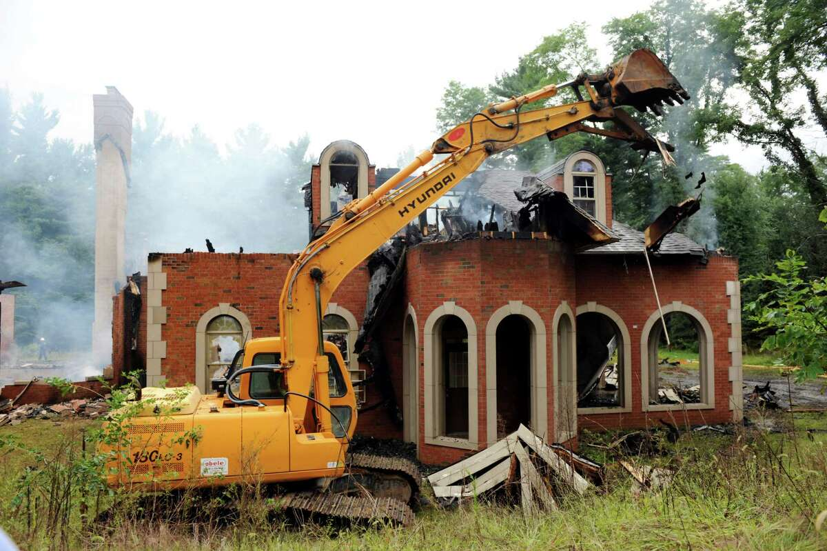 A backhoe tears down a mansion at 3494 Lydius St. destroyed by an early morning fire on Tuesday, Sept. 3, 2013, in Guilderland, N.Y. (Cindy Schultz / Times Union)