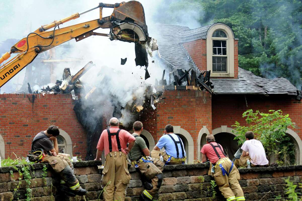 Firefighters rest as a backhoe tears down a mansion at 3494 Lydius St. destroyed by an early morning fire on Tuesday, Sept. 3, 2013, in Guilderland, N.Y. (Cindy Schultz / Times Union)