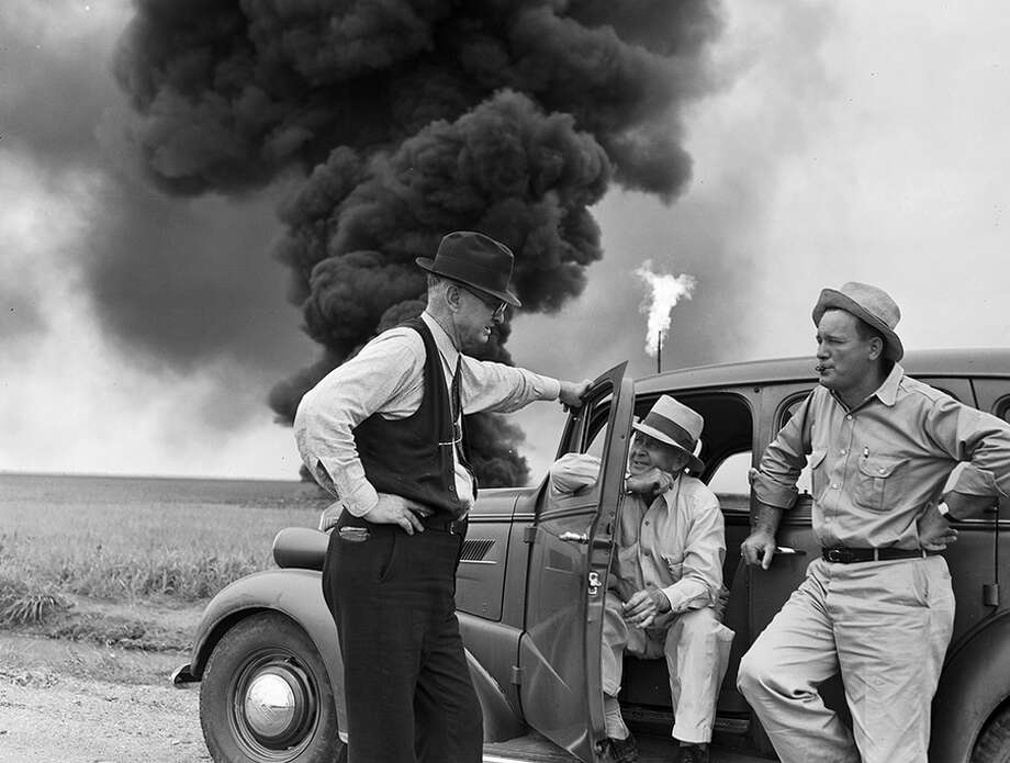 John Butler talks with two men while oil well fire burns in background.Photo: DeGolyer Library at Southern Methodist University