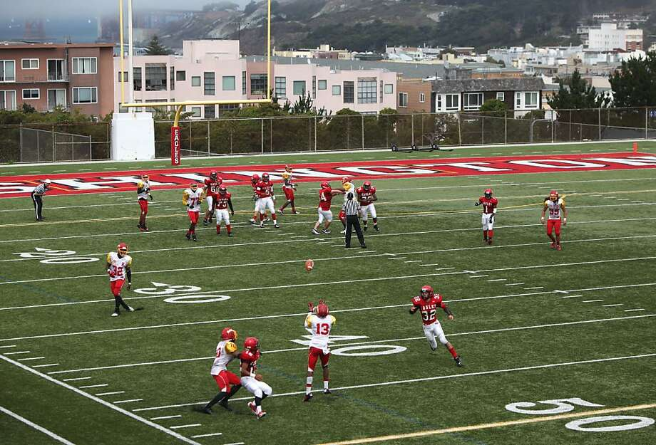 The Washington High School football team plays Berkeley High School as fog enshrouds the Golden Gate Bridge (upper left). Photo: Pete Kiehart, The Chronicle