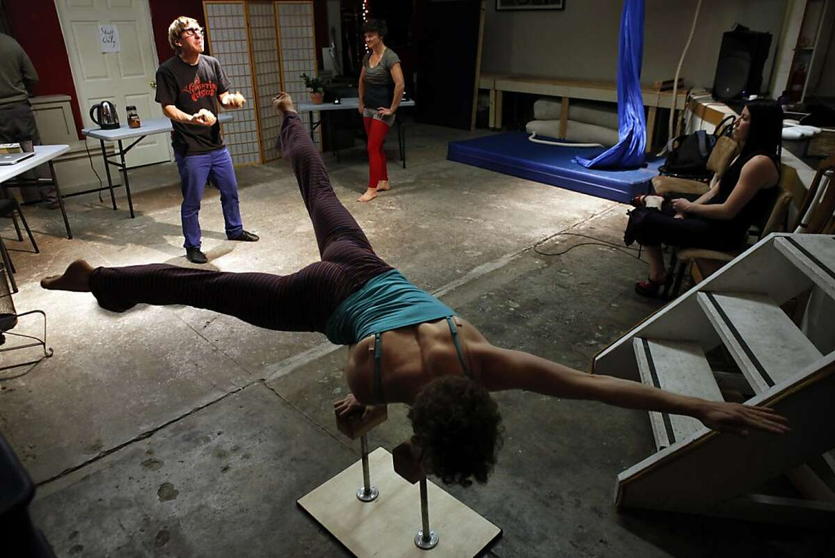 SAM Luckey (cq) does a one-handed hand stand during rehearsal of the Vespertine Circus in Oakland, Calif., on Tuesday, April 30, 2013. Oakland has become a major hub for circus arts. People come from all over the world to study in haphazard, organic