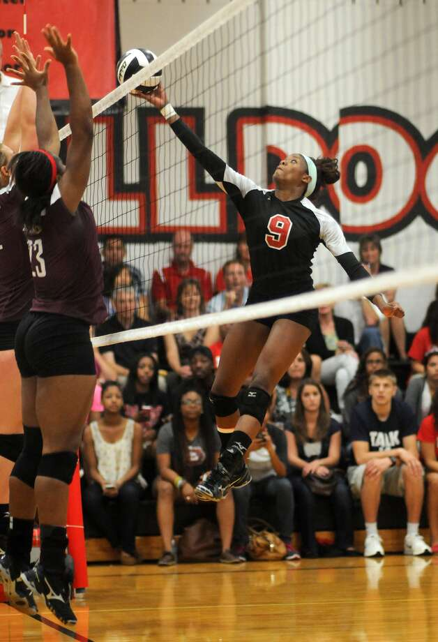 Ft Bend Austin junior outside hitter Cristen Coryatt, right, works at the net against Cinco Ranch senior Priscilla Ehieze. Photo: Jerry Baker, Freelance