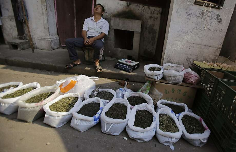 Decaffeinated presumably:A tea vendor snoozes after setting out his blends in a   back alley in Shanghai. Photo: Eugene Hoshiko, Associated Press