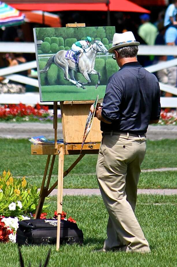 While watching the horses leave the paddock I took this picture of the artist capturing his view of the same area. Our intent was the same just different mediums. Friday, Aug. 2, 2013. (Linda Helfrich)