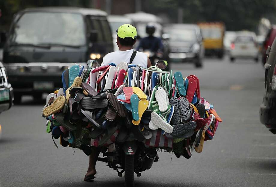 Where the rubber meets the road:A salesman peddles rubber flip-flops on his motorcycle in 