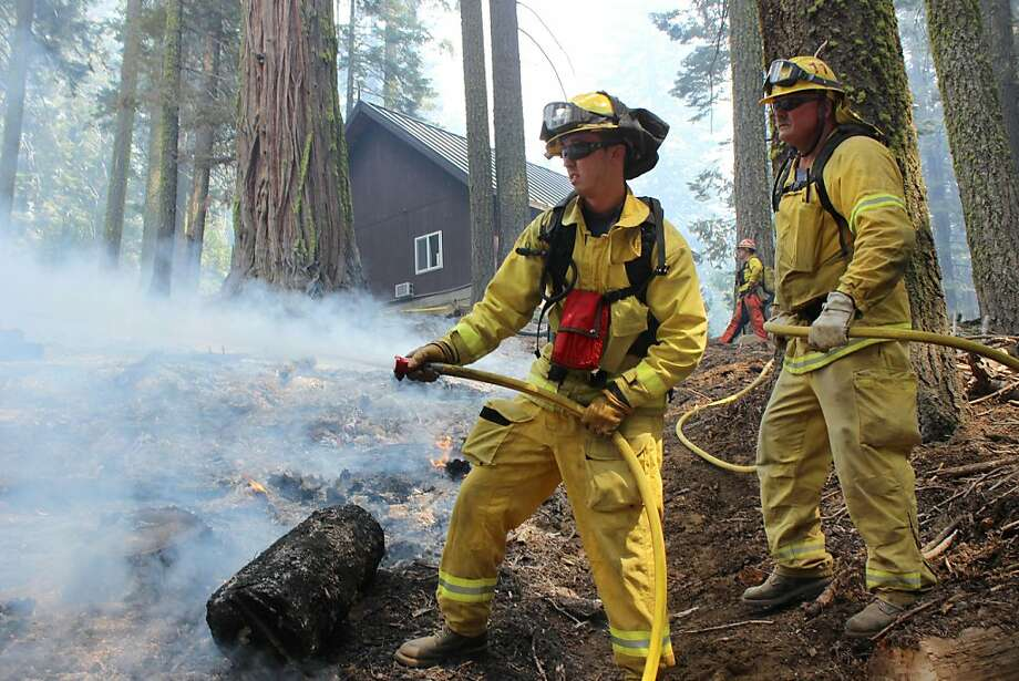Firefighters hose down a hot spot near a ranger station as they battle the Rim Fire in Yosemite National Park on Sunday. The blaze is 75 percent contained. Photo: Mike McMillan, Associated Press