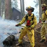 In this photo provided by the U.S. Forest Service, firefighters hose down a hotspot near a ranger station as they fight the Rim Fire in Yosemite National Park in California Sunday, Sept. 1, 2013. The massive wildfire is now 75 percent contained according to a state fire spokesman.