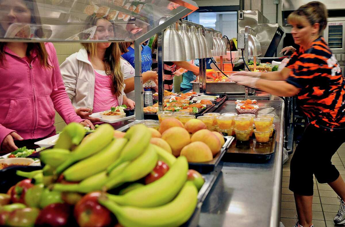 FILE - In this Tuesday, Sept. 11, 2012 file photo, students are given healthy choices on a lunch line at Draper Middle School in Rotterdam, N.Y. After just one year, some schools across the nation are dropping out of what was touted as a healthier federal lunch program, complaining that so many students refused the meals packed with whole grains, fruits and vegetables that their cafeterias were losing money. (AP Photo/Hans Pennink, File) ORG XMIT: NYR203