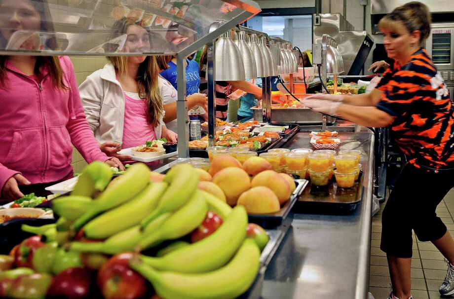 FILE - In this Tuesday, Sept. 11, 2012 file photo, students are given healthy choices on a lunch line at Draper Middle School in Rotterdam, N.Y. After just one year, some schools across the nation are dropping out of what was touted as a healthier federal lunch program, complaining that so many students refused the meals packed with whole grains, fruits and vegetables that their cafeterias were losing money. (AP Photo/Hans Pennink, File) ORG XMIT: NYR203 Photo: Hans Pennink / FR58980 AP