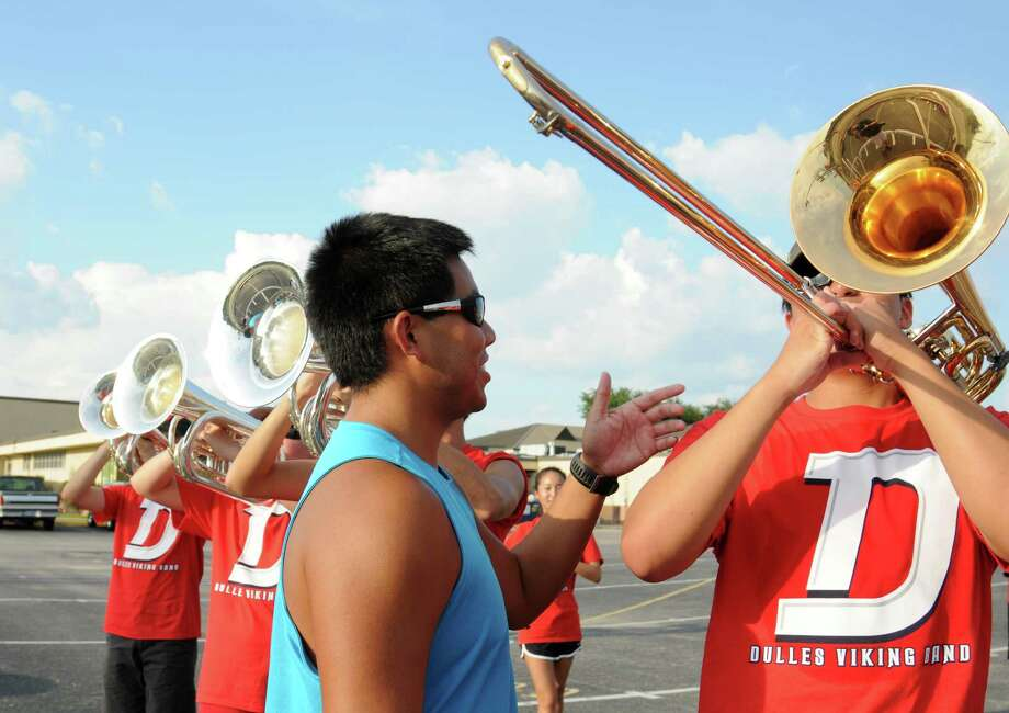 Dulles High School band visual instructor Russell Zavalla helps band member Mark Llamas during rehearsal. / Freelance