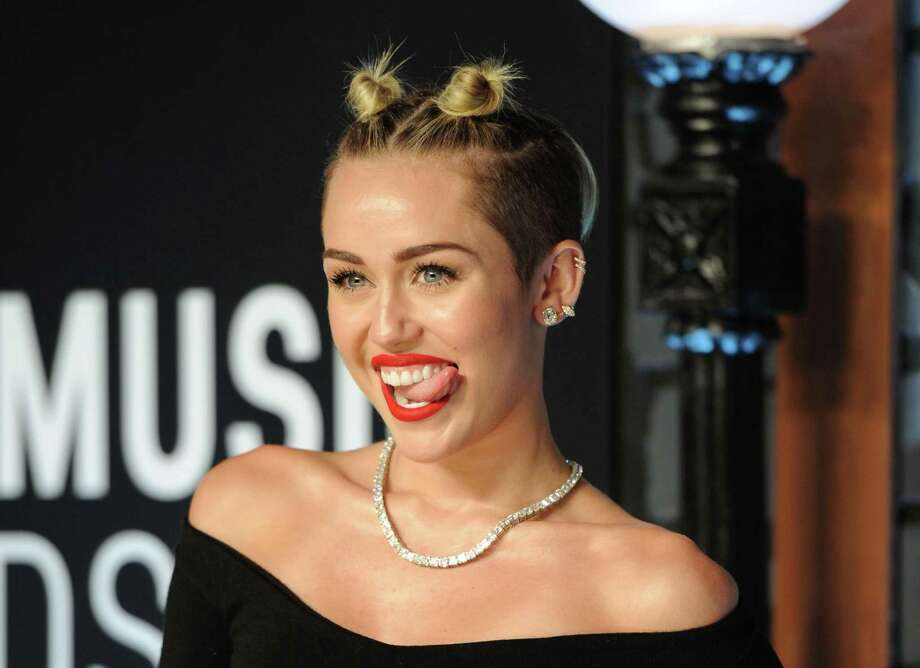 "FILE - This Aug. 25, 2013 file photo shows singer Miley Cyrus at the MTV Video Music Awards in the Brooklyn borough of New York.  Cyrus says in an interview clip that she doesn't listen to the negative comments regarding her performance on the MTV Video Music Awards. The pop star says she felt she and Robin Thicke were making history with the risque performance of their hits ""We Can't Stop"" and ""Blurred Lines."" The comments were Cyrus' first since the Aug. 25 show. The clip was recorded last week and posted Tuesday morning on MTV's website. Cyrus compares the performance to that of Madonna and Britney Spears, who once kissed on air.  (Photo by Evan Agostini/Invision/AP, File) ORG XMIT: NYET108 Photo: Evan Agostini / Invision"