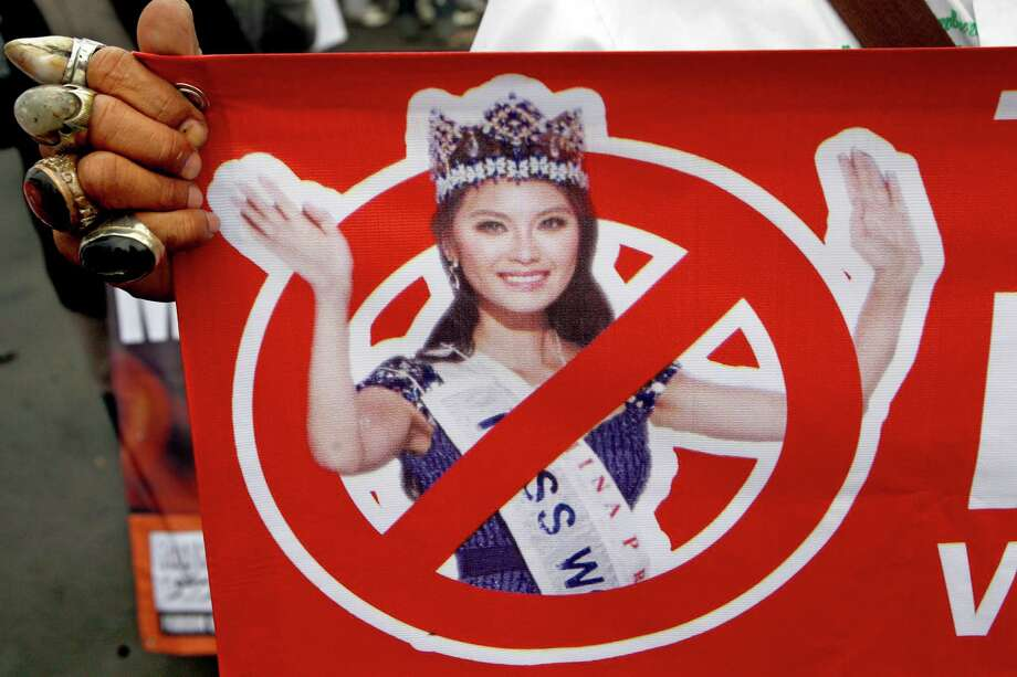A Muslim man holds a banner bearing a defaced image of Miss World 2012 Yu Wenxia of China during a protest calling for the cancellation of Miss World pageant in Jakarta, Indonesia, Tuesday, Sept. 3, 2013. Hardliners in the world's most populous Muslim country staged the protest Tuesday, demanding the government to ban the pageant that is scheduled to be held later this month saying that it goes against moral values. (AP Photo/Achmad Ibrahim) ORG XMIT: JAK104 Photo: Achmad Ibrahim / AP