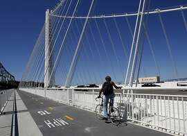 A cyclist stopped to admire the view from near the suspension tower Tuesday September 3, 2013. The Alexander Zuckermann bicycle and pedestrian path on the new eastern span of the Oakland Bay Bridge was opened Tuesday.