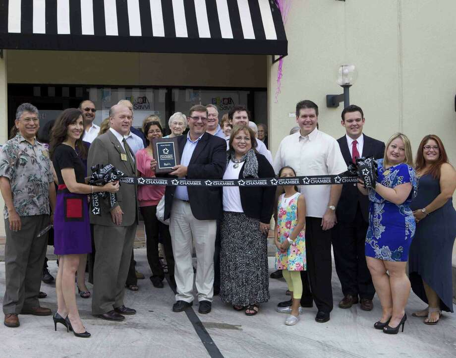 North San Antonio Chamber of Commerce representatives give a plaque to co-owners Stephan and Mary Ann Samuelson during the grand opening of Pixel Savvi Aug. 21 at The Elms Shopping Center, 11854 Wurzbach Road.