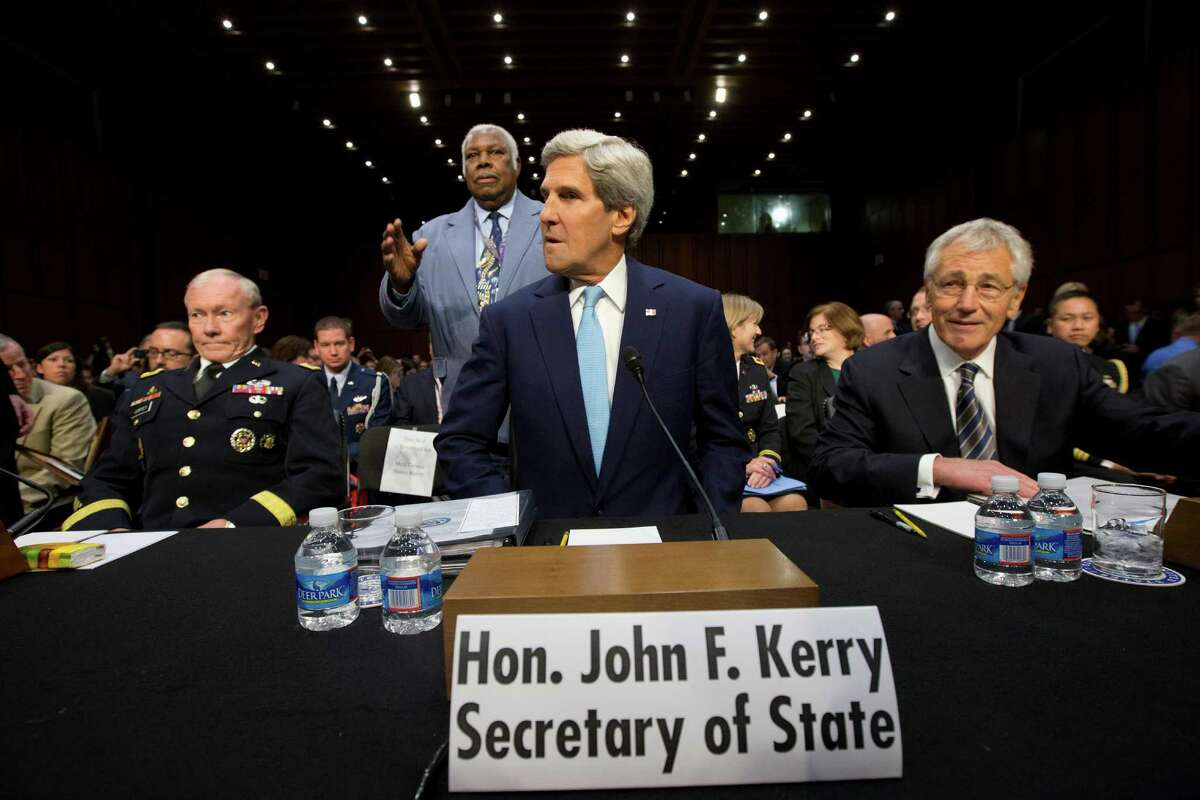 Secretary of State John Kerry, center, flanked by Joint Chiefs Chairman General Martin E. Dempsey, left, and Defense Secretary Chuck Hagel, takes his seat on Capitol Hill in Washington, Tuesday, Sept. 3, 2013, prior to testifying before a Senate Foreign Relations Committee hearing on Syria.