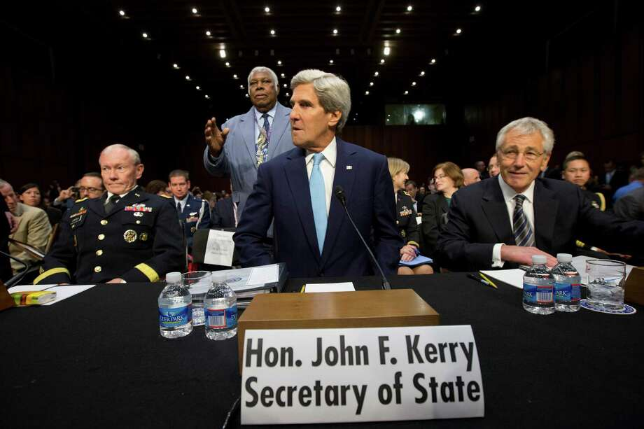 Secretary of State John Kerry, center, flanked by Joint Chiefs Chairman General Martin E. Dempsey, left, and Defense Secretary Chuck Hagel, takes his seat on Capitol Hill in Washington, Tuesday, Sept. 3, 2013, prior to testifying before a Senate Foreign Relations Committee hearing on Syria. Photo: Jacquelyn Martin