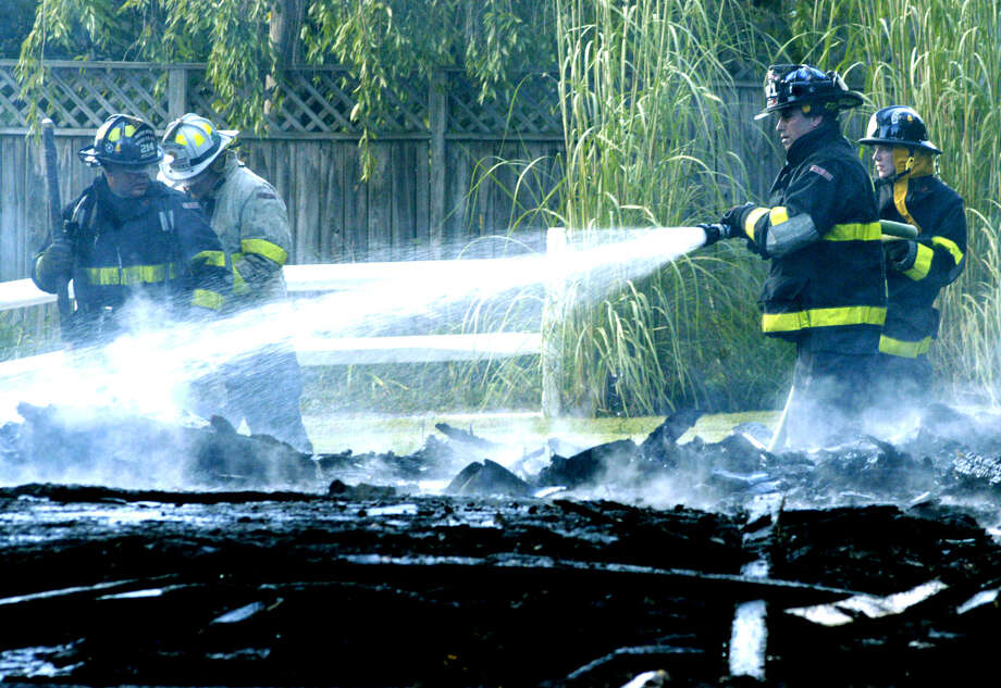 Volunteer firefighters from Water Witch Hose Co. No. 2 spray down remnants of a garage which exploded and was rapidly engulfed in flames Tuesday afternoon about 5 p.m.  at 10 Wellsville Avenue in New Milford. Photo: Norm Cummings