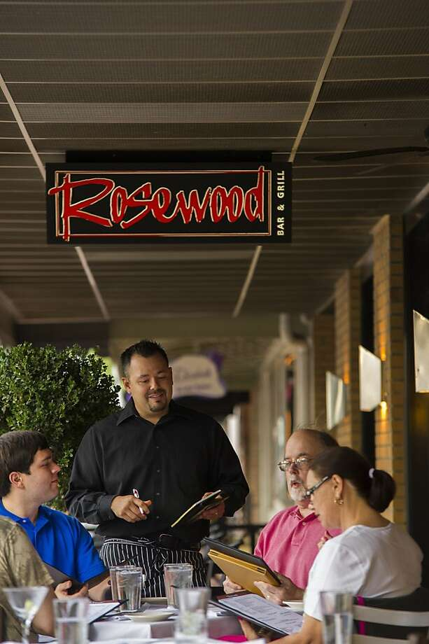 A family dines outdoors at Rosewood Bar and Grill on South School Street, a pleasant experience now, as summer turns to fall. Photo: Dan Evans