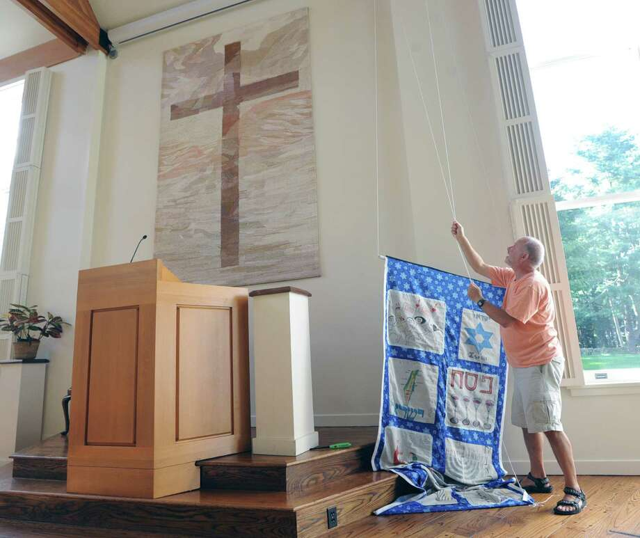 Dahni Nisinzweig, a member of Congregation Shir Ami, prepares to hang a banner to be used as part of the upcoming Rosh Hashanah service at the Round Hill Community Church in Greenwich, Tuesday afternoon, Sept. 3, 2013. Jenny Lake of Congregation Shir Ami, said that services will be held in the church located at 395 Round Hill Road, Greenwich, at 7 p.m. Wednesday and 10 a.m. Thursday. Photo: Bob Luckey / Greenwich Time