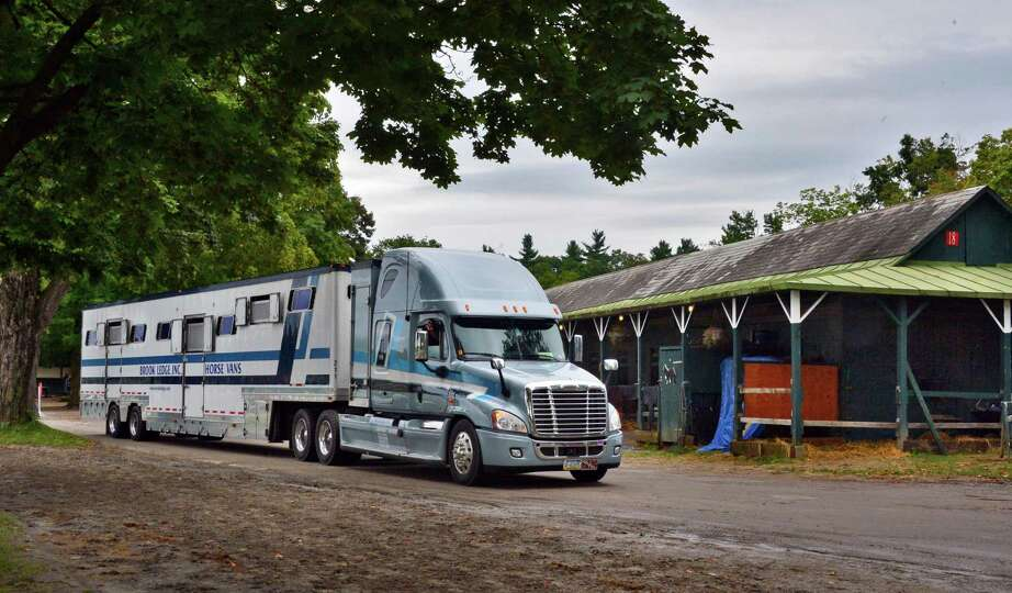 Trucks arrive to take away horses and equipment from backstretch barns Tuesday morning, Sept. 3, 201