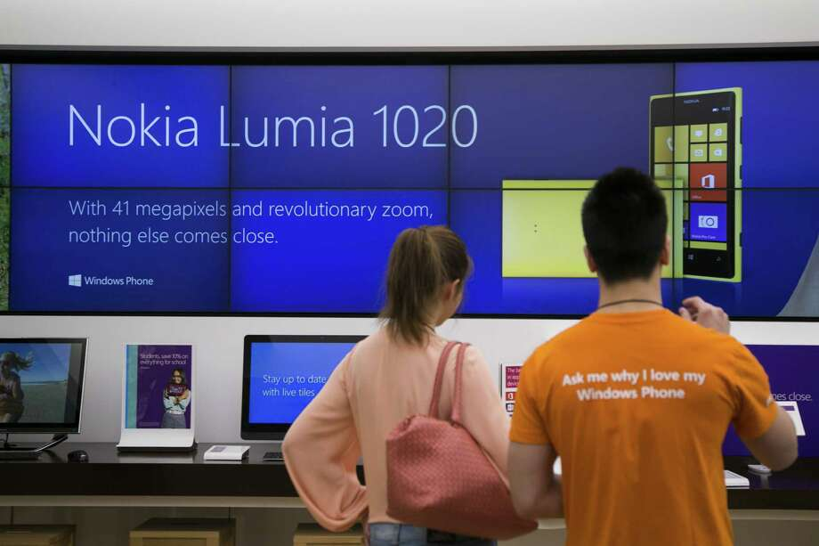 Sales associate Jacky Hom assists customer Katie Guo with a product demonstration of the Nokia Lumia 1020 phone at a Microsoft store in Boston. Microsoft Corp. has agreed to buy Nokia handset unit and license its patents for $7.2 billion. Photo: Bloomberg