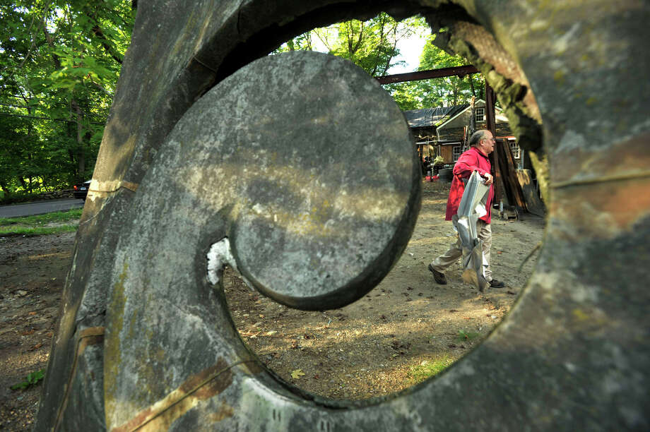 Sculptor James Knowles is seen through one of his pieces of art attempting to construct another at his studio next to his home in Stamford on Tuesday, Sept. 3, 2013. Photo: Jason Rearick / Stamford Advocate