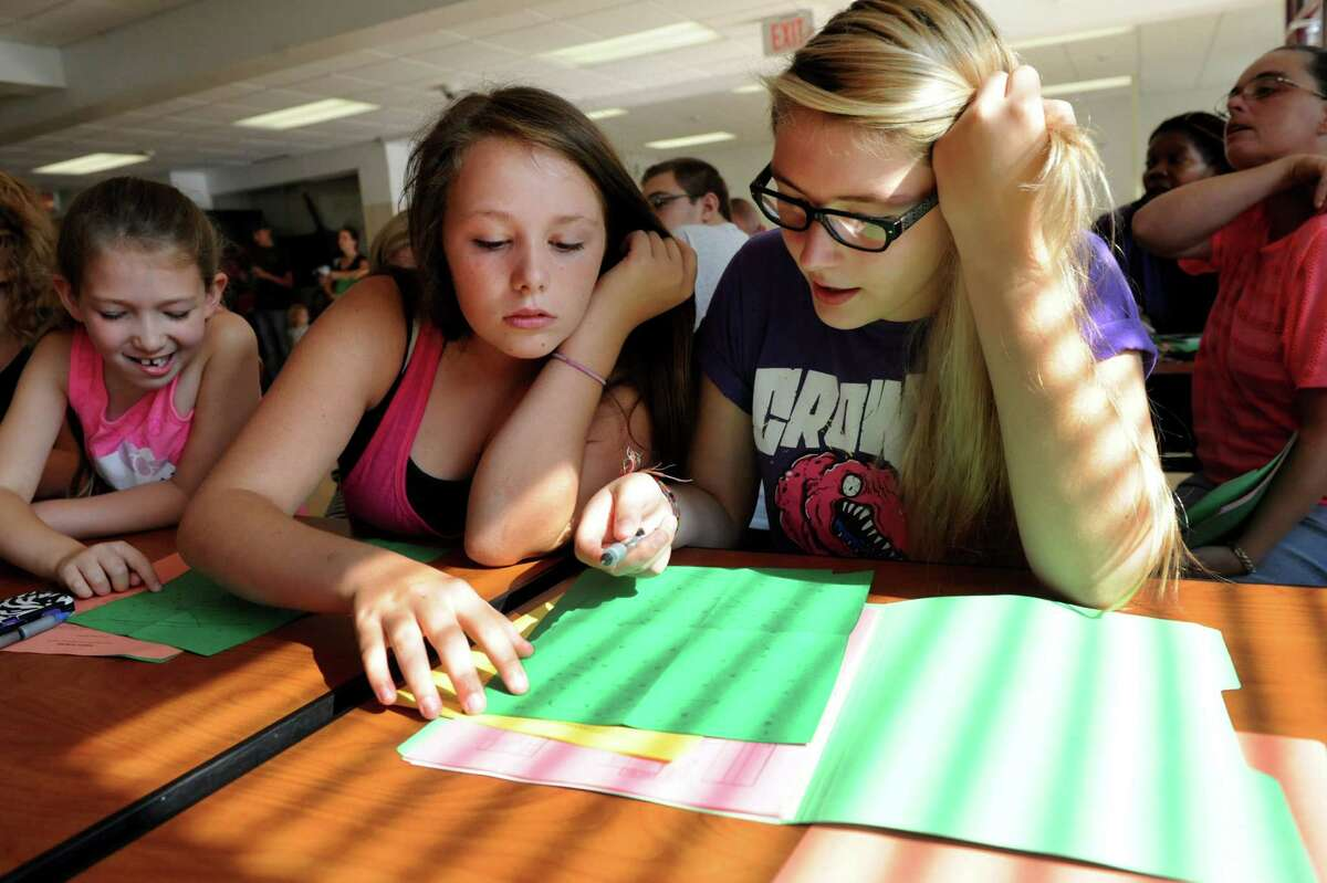Freshmen Breanna Mysliwiec, 14, center, and Karley Culliton, 14, right, work on an exercise during Freshman Academy on Wednesday, Aug. 28, 2013, at Lansingburgh High School in Troy, N.Y. At left is Samantha Culliton, 7, Karley's sister. The school's new Freshman Academy aims to improve student performance as they transition to high school. (Cindy Schultz / Times Union)