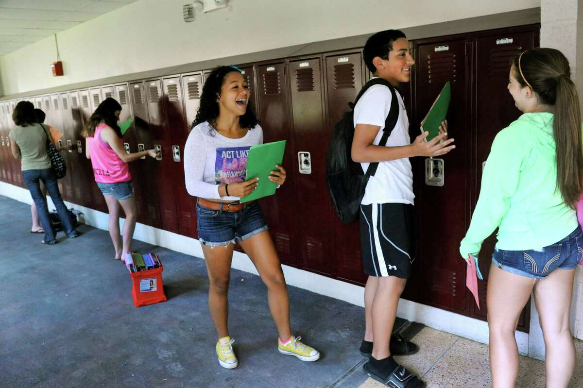 Freshmen Serena Gates, 14, center, and Guillermo Chacon, 14, second from right, greet Alli Christian, 14, right, as they find their lockers during Freshman Academy on Wednesday, Aug. 28, 2013, at Lansingburgh High School in Troy, N.Y. The school's new Freshman Academy aims to improve student performance as they transition to high school. (Cindy Schultz / Times Union)