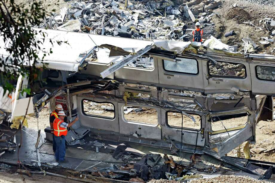 File - This Sept. 14, 2008 file photo shows investigators photographing the mangled inside of a Metrolink  commuter train in Chatsworth, Calif. Despite a rash of deadly train crashes, the railroad industry's allies in Congress are trying to push back the deadline for installing technology to prevent the most catastrophic types of collisions to at least 2020, half a century after accident investigators first called for such safety measures.  (AP Photo/Richard Vogel, File) ORG XMIT: WX102 Photo: Richard Vogel / AP