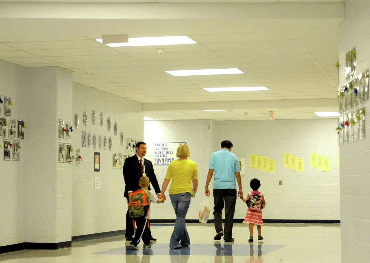 Principal Jeff Palmer, far left, greets pre-k students and their parents Tuesday morning, Sept. 3, 2013, during the first day of school at Van Rensselaer Elementary School in Rensselaer, NY. (Paul Buckowski / Times Union)