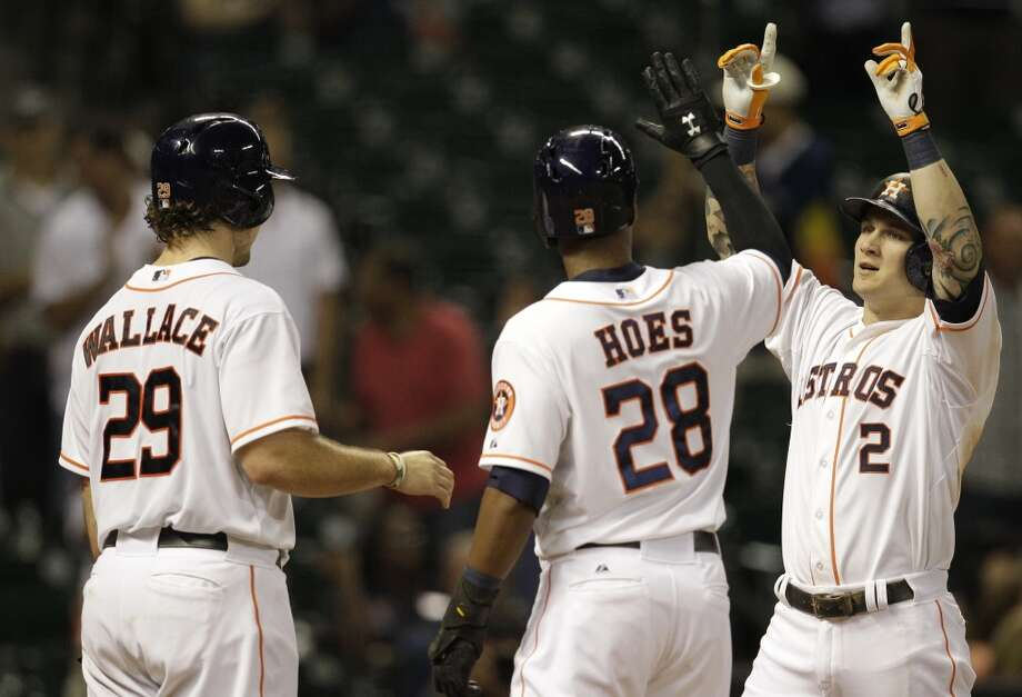 Astros outfielder Brandon Barnes is congratulated by teammates Brett Wallace and L.J. Hoes after hitting a three-run home run that tied the game in the ninth inning against the Twins. Photo: Melissa Phillip, Houston Chronicle