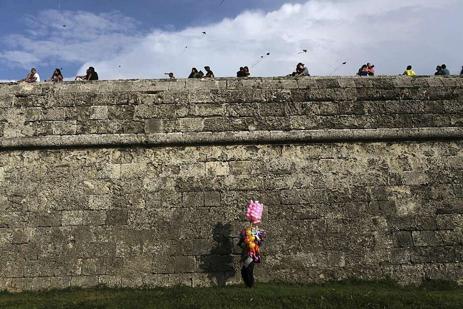 TOPSHOTS A man sales sweet cotton as others sit by the fortress walls in the port city of Cartagena, Colombia during kite season on September 2, 2013. AFP PHOTO/Joaquin SarmientoJoaquin SARMIENTO/AFP/Getty Images Photo: Joaquin Sarmiento, AFP/Getty Images