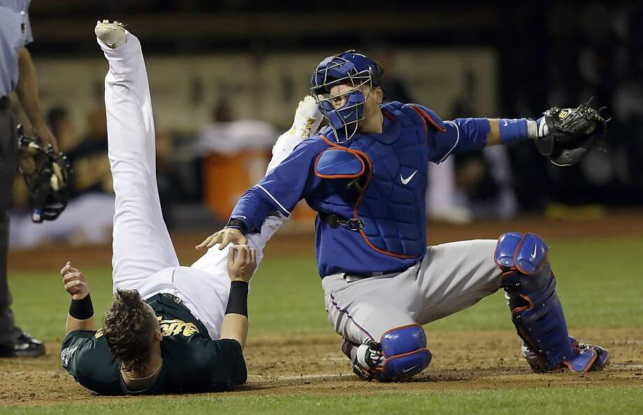 Texas catcher A.J. Pierzynski reaches toward Josh Donaldson after he tagged out the A's third baseman in the third inning. Photo: Jeff Chiu, Associated Press