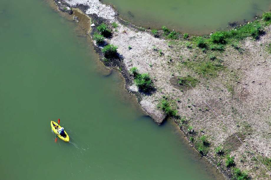 A kayaker paddles Aug. 24, 2013 through the Mission Reach section of the San Anotnio River south of downtown. Photo: William Luther, San Antonio Express-News / © 2013 San Antonio Express-News