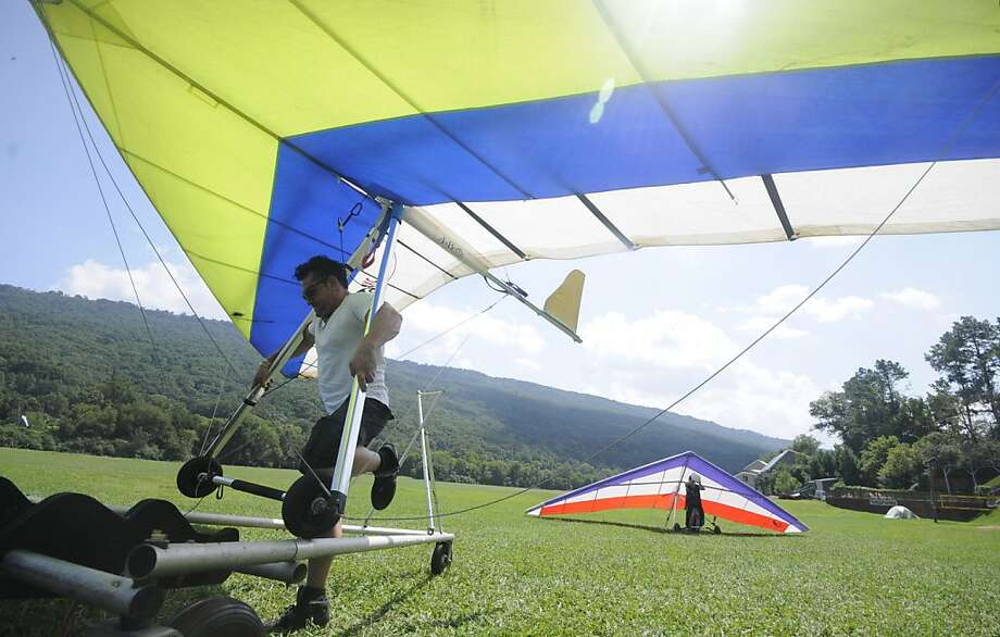 "Dana Daniels, a mobile disc jockey from Atlanta, moves his glider into position for transport after a 20- minute flight from the top of Lookout Mountain Flight Park, Tuesday, Sept. 3, 2013. ""I got about 1,000-feet above the mountain just after take-off,"" Daniels said. Jen Richards, back, and employee in the pro-shop atop Lookout Mountain, walks her glider to the break-down area after landing.  (AP Photo/Chattanooga Times Free Press, Tim Barber) Photo: Tim Barber, Associated Press"