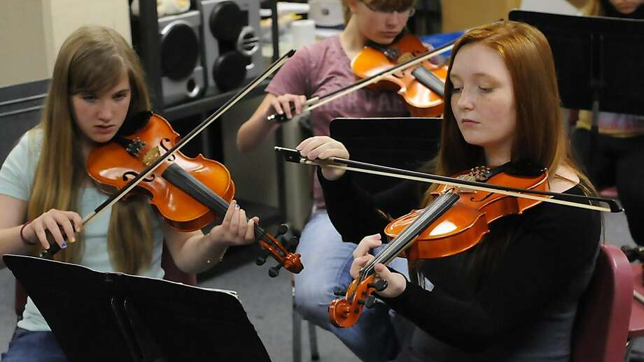 Kaitlyn Bellew, at left, and Zoe Vance play their violins during class Tuesday Sept. 3, 2013 at Verity Middle School in Ashland, Ky. The school orchestra has been awarded a Program Of Excellence gold level award from the Kentucky Music Educators Association. (AP Photo/The Independent, Kevin Goldy) Photo: Kevin Goldy, Associated Press
