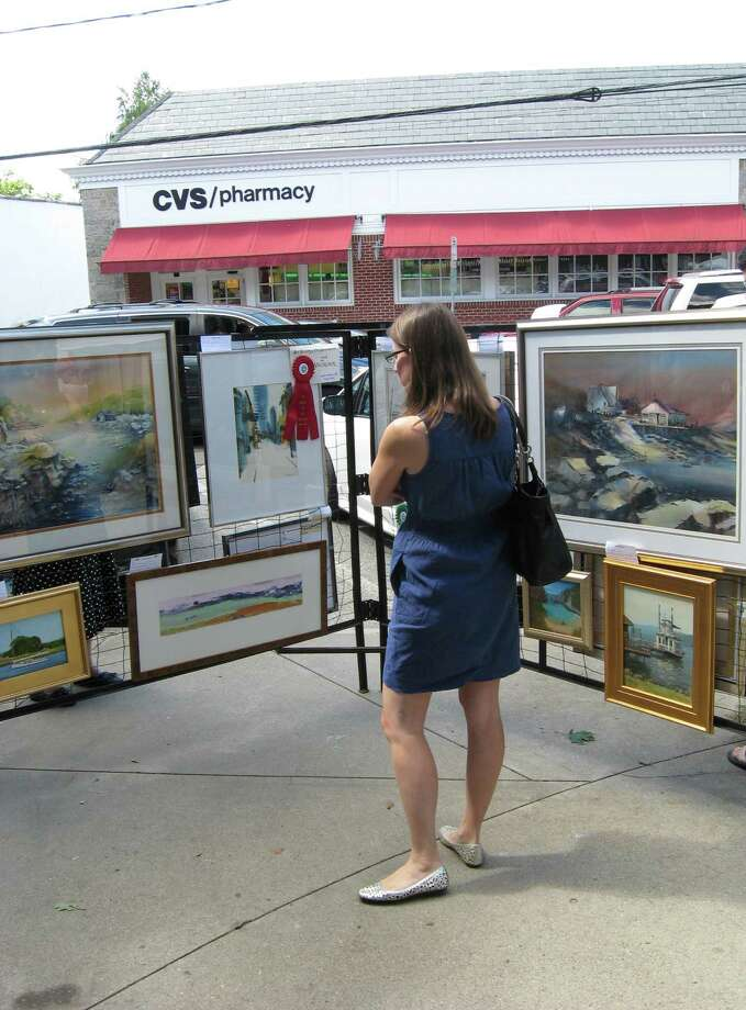 The Art Society of Old Greenwich will hold its 62st Annual Sidewalk Art Show and Sale on Saturday, Sept. 7, and Sunday, Sep. 8, from 9 a.m. to 5 p.m.  Above, an art lover admires a work at last year's show. Photo: Contributed Photo