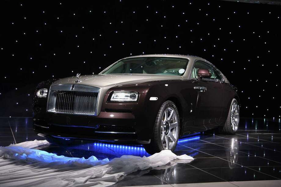 "The two-door, four-seat Wraith has the unmistakable and imposing front end of a Rolls with a rakish slanted roof in the rear. It's the most powerful Rolls ever built, with a 6.6-liter V12 engine that gets 624 horsepower. Inside, there's a new system that uses GPS data and navigation to scan the road ahead and automatically pick out the right gear from the eight-speed transmission. Another first is a rotary controller for the dashboard screen that has a touch-sensitive pad that lets you ""write"" who you want to call or where you want to go with your finger. Want more? You can have 1,340 fiber optics sewn into the headliner to make it look like you're driving under a starry sky. Pricing will start around $300,000 when the Wraith goes on sale later this year. Photo: Ralf Juergens, Getty Images / 2013 Ralf Juergens"