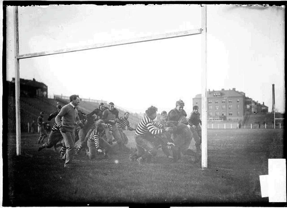 Image of University of Chicago-University of Texas football game in 1904 played at Marshall Field in Chicago, Illinois. A referee is watching the play. Empty bleachers are visible in the background.